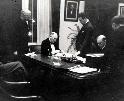 Lord Riverdale (seated, left) and Prime Minister William Lyon Mackenzie King (seated, right) sign the British Commonwealth Air Training Plan Agreement on December 17, 1939. PHOTO: DND Archives