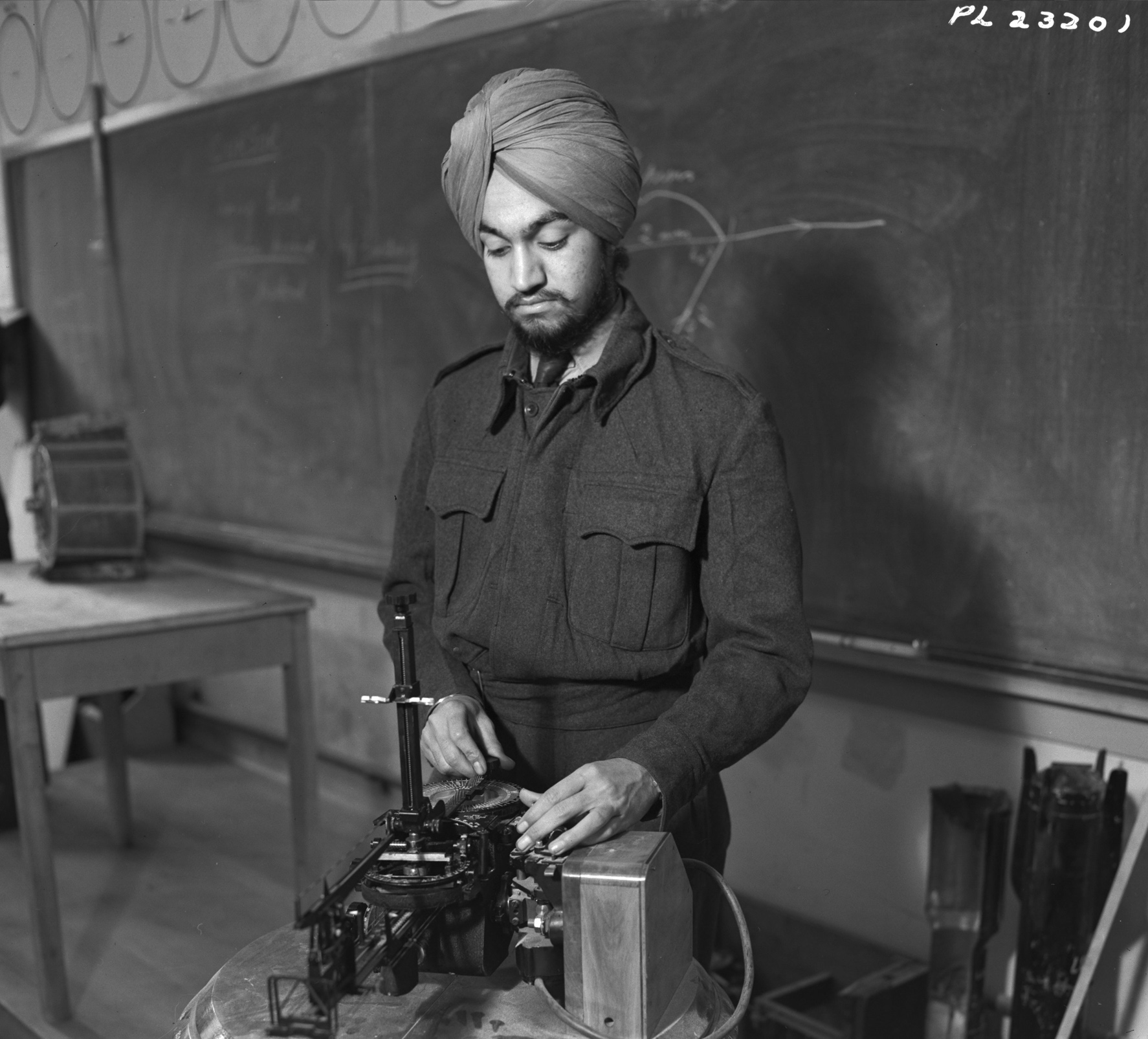Leading Aircraftman Rajinder Singh Sandhu, from Pakho Pur, India, examines the mechanics of a bomb sight at No. 41 Service Flying Training School at RCAF Weyburn, Saskatchewan. PHOTO: DND Archives, PL-23201