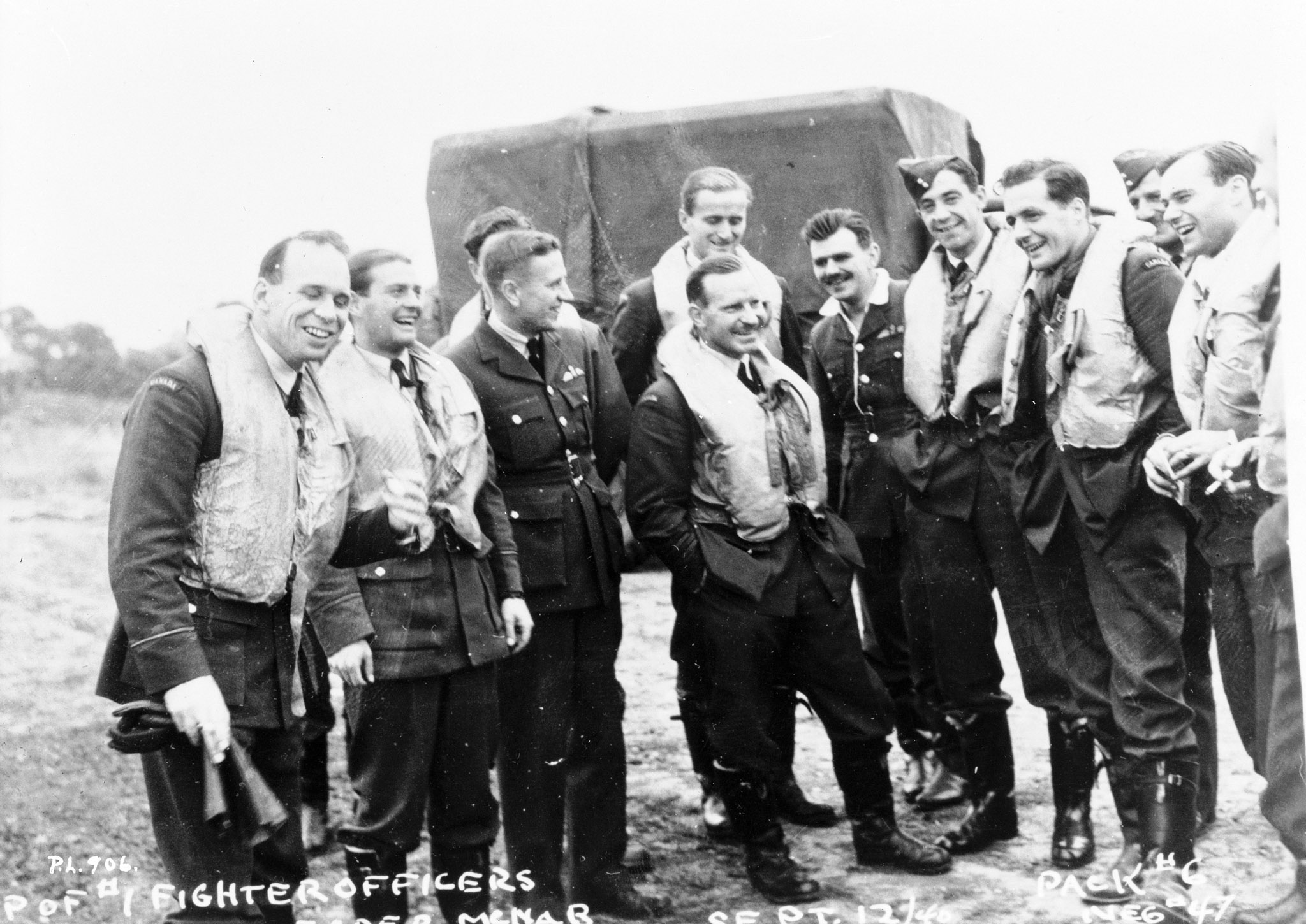 Le commandant d'aviation Ernest A. McNab et plusieurs de ses pilotes se détendent et posent pour la photo pendant la Bataille d'Angleterre (de gauche à droite) : le lieutenant d'aviation William P. Sprenger, le lieutenant d'aviation Otto John Peterson, le capitaine d'aviation W.R. Pollock (adjudant), le lieutenant d'aviation Paul Brooks Pitcher, le commandant d'aviation McNab, le lieutenant d'aviation Peter William Lochnan, le capitaine d'aviation Edwin Michael Reyno, le lieutenant d'aviation Eric Walter Beardmore, le lieutenant d'aviation S.T. Blaikloch (officier du renseignement) et le lieutenant d'aviation Robert William Norris. PHOTO : Bibliothèque et Archives Canada, PL-906