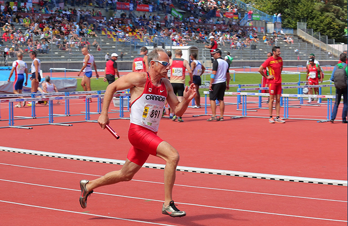 slide - Major Serge Faucher, a member of the Royal Canadian Air Force from the Directorate of Air Programs at National Defence Headquarters in Ottawa, Ontario, competes in the 4 X 100-metre relay at the 2015 World Masters Athletics Championships.