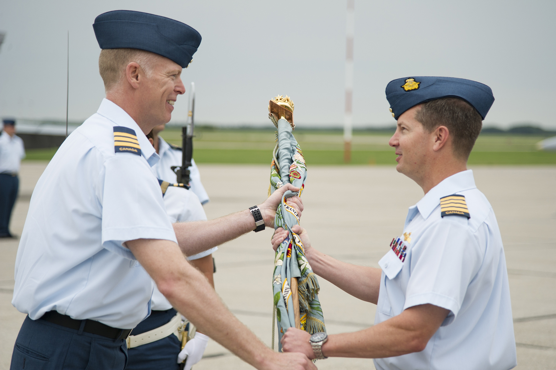 slide - Colonel Eric Kenny (right), commander of 4 Wing, presents the 401 Tactical Fighter Squadron colour to Lieutenant Colonel Joseph Mullins, commanding officer of the newly re-established squadron, on June 30, 2015.