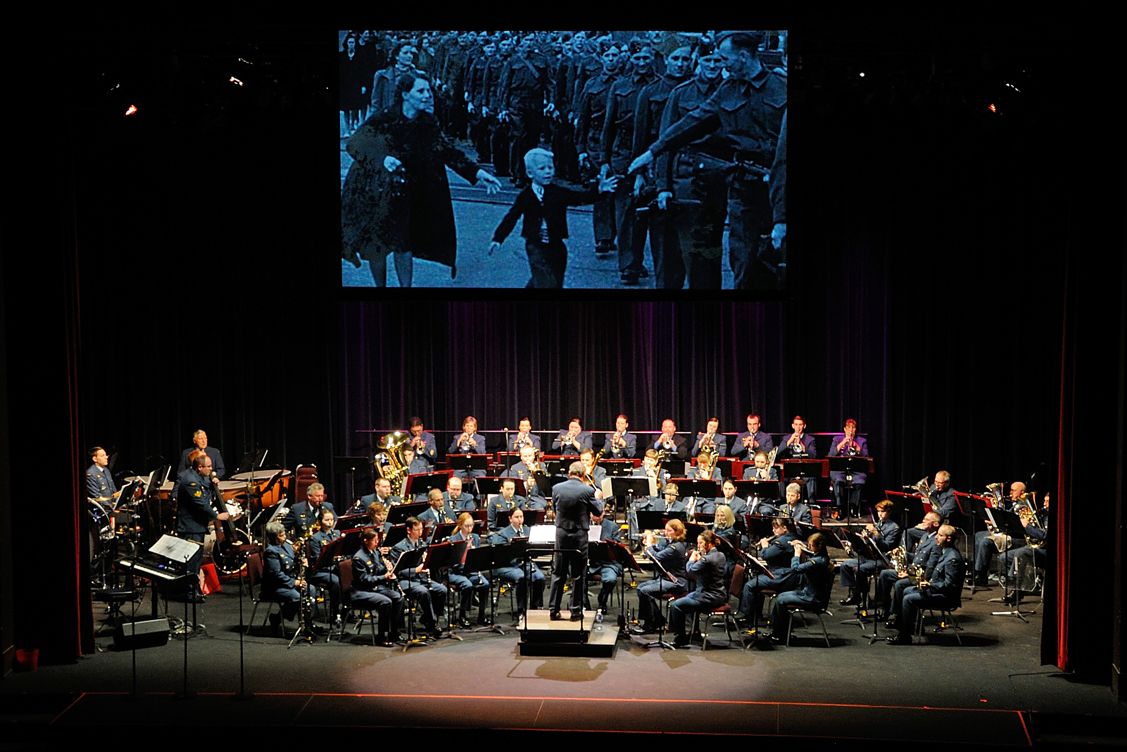 "In November 2014, the 22 Wing Volunteer Band performs during the wing's annual musical tribute in North Bay, Ontario. The backdrop for the performance is the iconic 1940 Canadian photograph ""Wait for Me Daddy"", by Claude P. Dettloff. The charity sponsor and beneficiary for the concert, which included a number of performers, was the Special Olympics Ontario 2015 Provincial Winter Games. PHOTO: Corporal Joseph Morin"