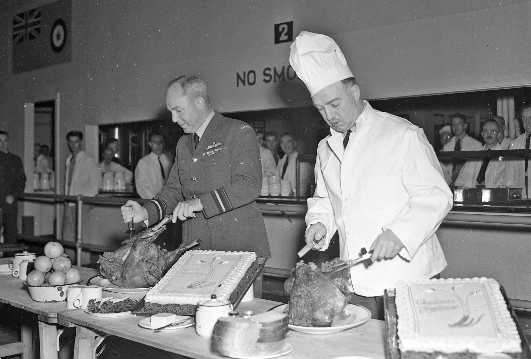 Group Captain H.O. McDonald (right), the commanding officer of the Royal Canadian Air Force's No. 1 Manning Depot in Toronto, Ontario, discarded his air force uniform for a chef's tall white hat and jacket when airmen at the station were served an early Christmas dinner. The Yuletide meal, complete with all the trimmings, was served by the officers and non-commissioned officers of the Manning Depot. Air Vice-Marshal G.O. Johnson (left), the air officer commanding No. 1 Training Command, RCAF, joined Group Captain McDonald in serving two of the hundreds of turkeys that disappeared during the meal held on December 22, 1942. PHOTO: DND Archives