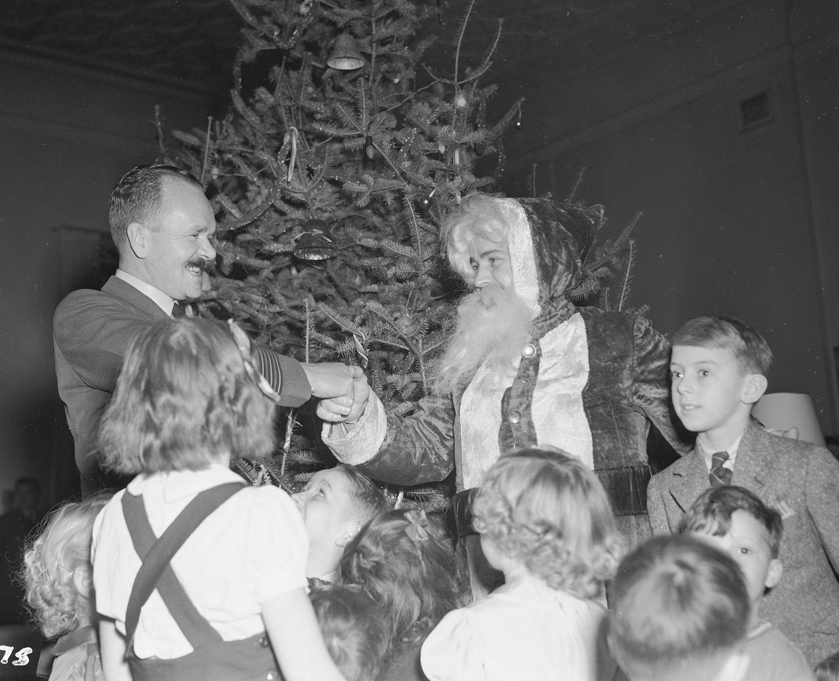 Wing Commander A. J. Hanchet-Taylor welcomes Santa Claus to the airmen's lounge at No. 6 Initial Training School in Toronto on December 24, 1942. Several children of Royal Canadian Air Force airmen wait to talk to the jolly old elf. PHOTO: DND Archives