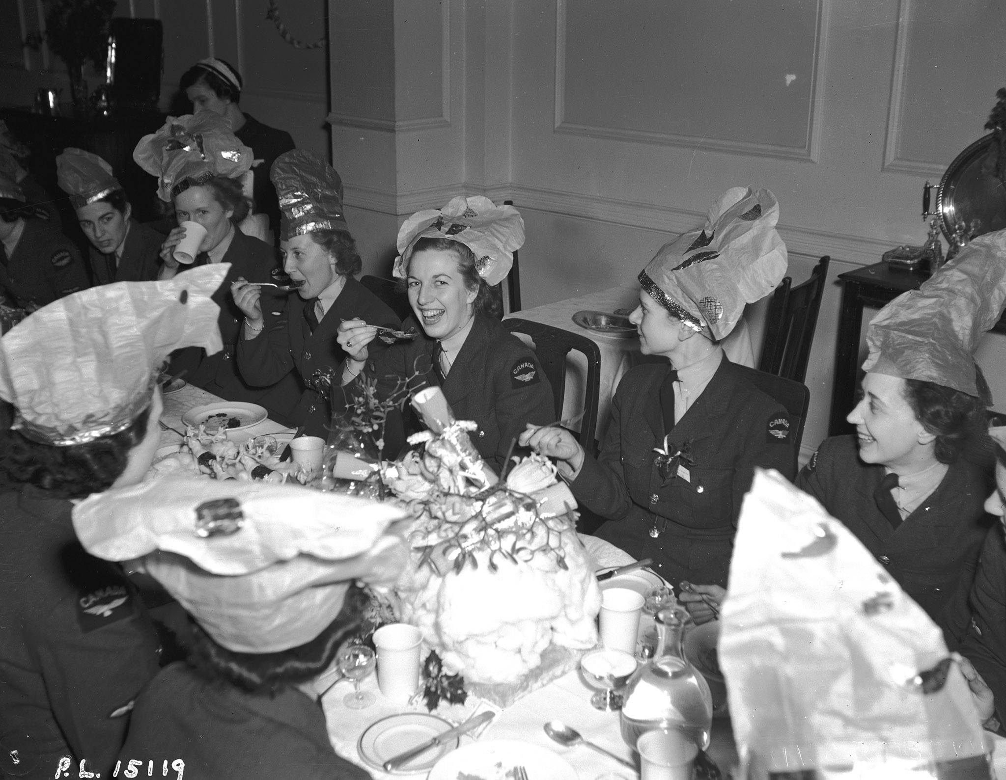 "Members of the Royal Canadian Air Force Women's Division share a Christmas dinner in the United Kingdom on December 23, 1942. Note the ""lovely table decoration of reindeers and a huge sleigh"". From left to right are Leading Aircraftwoman M. McKinnon, Leading Aircraftwoman Peggy Douglas and Leading Aircraftwoman L. Levens. PHOTO: DND Archives"