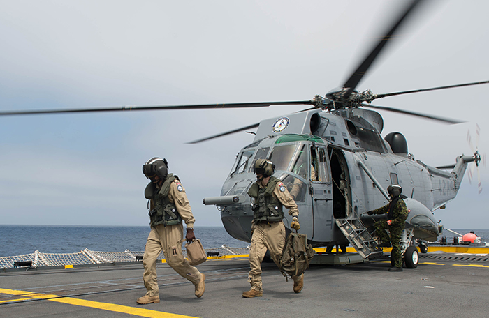 slide - The aircrew of a CH-124 Sea King helicopter deployed with Her Majesty's Canadian Ship Winnipeg swap crews
