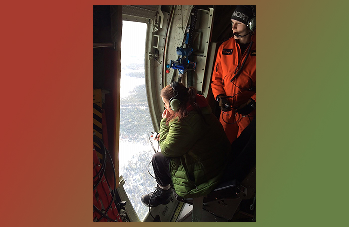 slide - Volunteer Civil Air Search and Rescue Association (CASARA) members lean into the spotter's window of a 413 Transport and Rescue Squadron CC-130H Hercules aircraft during January 24, 2016, spotter training over an area northeast of Gander, Newfoundland and Labrador.