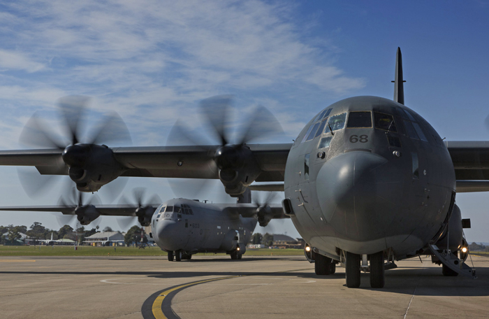 slide - Under a blue sky with light clouds, two Hercules aircraft are on the tarmac, one behind the other, with their propellers spinning.