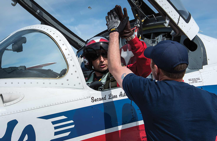 "slide - A pilot seated in an aircraft and a technician standing on the ground share a ""high five""."
