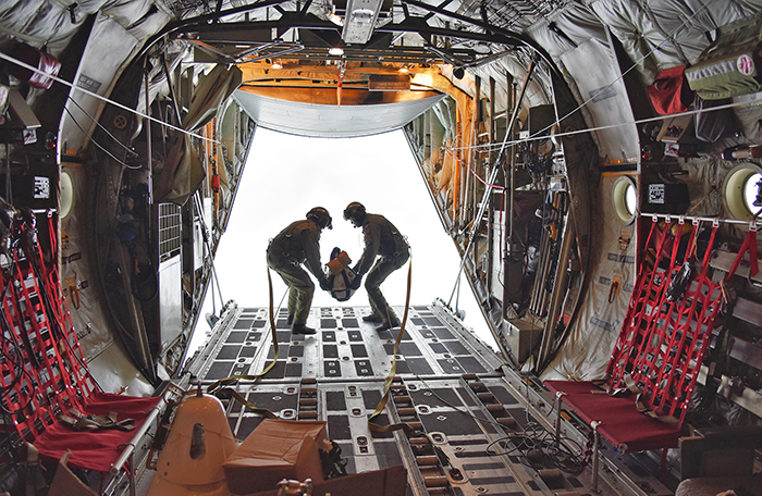 slide - Looking down the tunnel-like interior of a military aircraft to the open rear ramp where two military personnel hold a large object between them on the edge of the ramp.