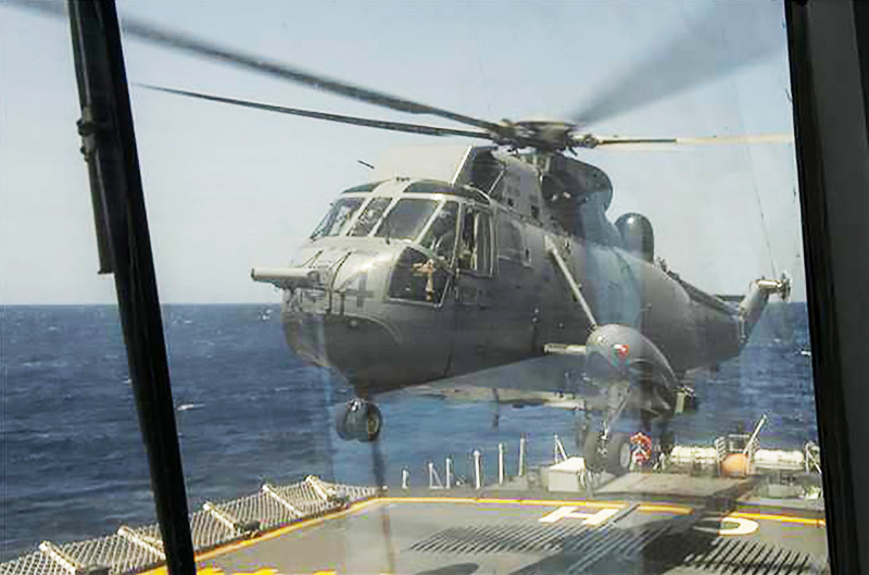 A photograph shot through glass of a helicopter landing on the deck of a ship.