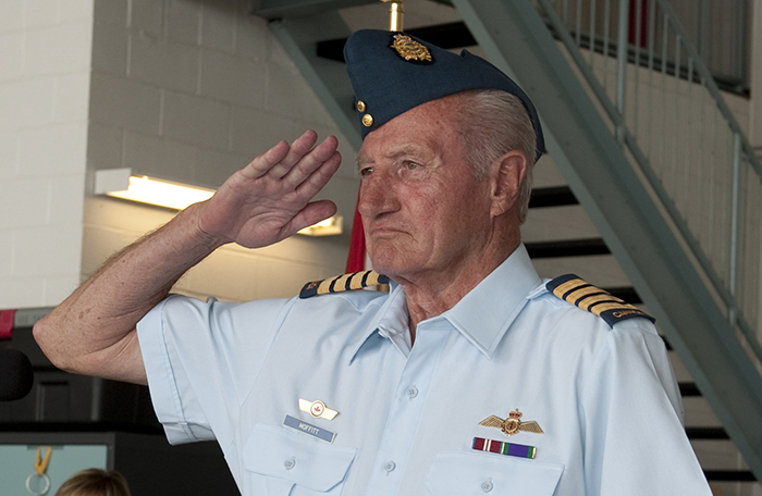 slide - A head and shoulders photo of an older man in an air force uniform, saluting.