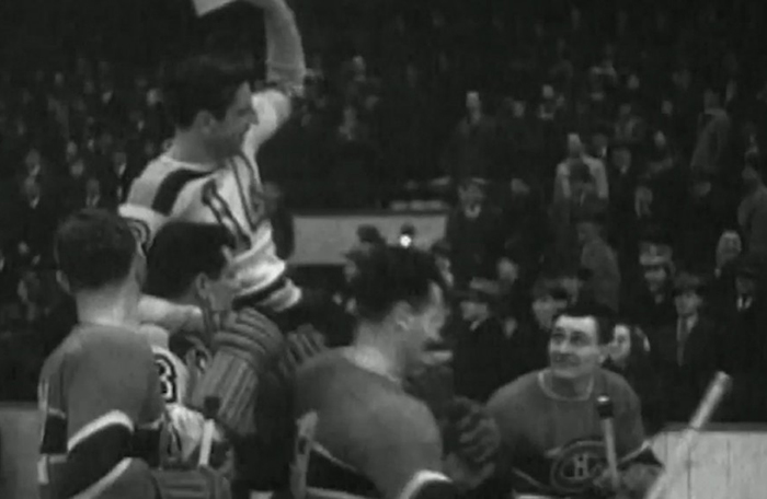 slide - An old black and white photo of a hockey player being carried on the shoulders of other hockey players.