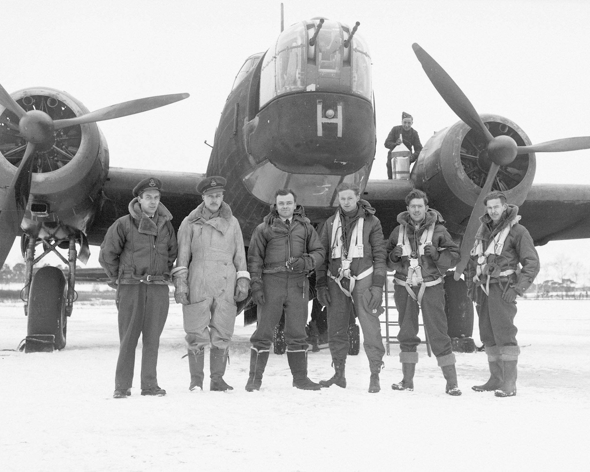"The all-Canadian crew of 419 Squadron Vickers Wellington Mk 1C bomber (""H"" for Harry) gather for a photograph on their Royal Canadian Air Force base in England on February 9, 1942. From left are Squadron Leader F.W.S. Turner (Ganges, British Columbia); Pilot Officer K.E. Hobson (Winnipeg, Manitoba); Flight Sergeant G.P. Fowler (Victoria, British Columbia); Flight Sergeant C.A. Robson (Truro, Nova Scotia); Flight Sergeant N.G. Arthur (Edmonton, Alberta); and Flight Sergeant H.T. Dell (Niagara Falls, Ontario). The groundcrew member on the wing is unidentified. PHOTO: DND Archives, PL-7096"