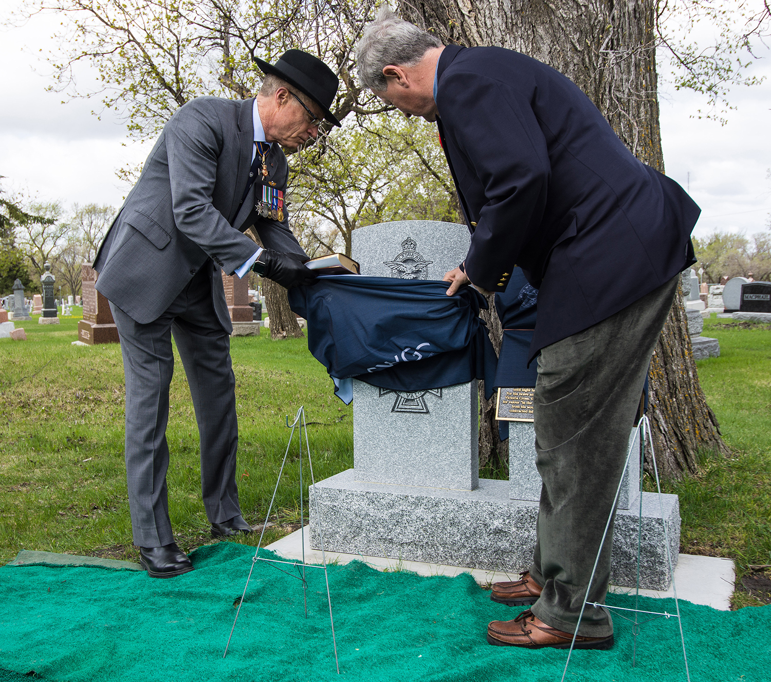 Brigadier-General (retired) David Kettle (left), and Mr. Alan Adams, the nephew of Second Lieutenant Alan McLeod, unveil the new grave marker.