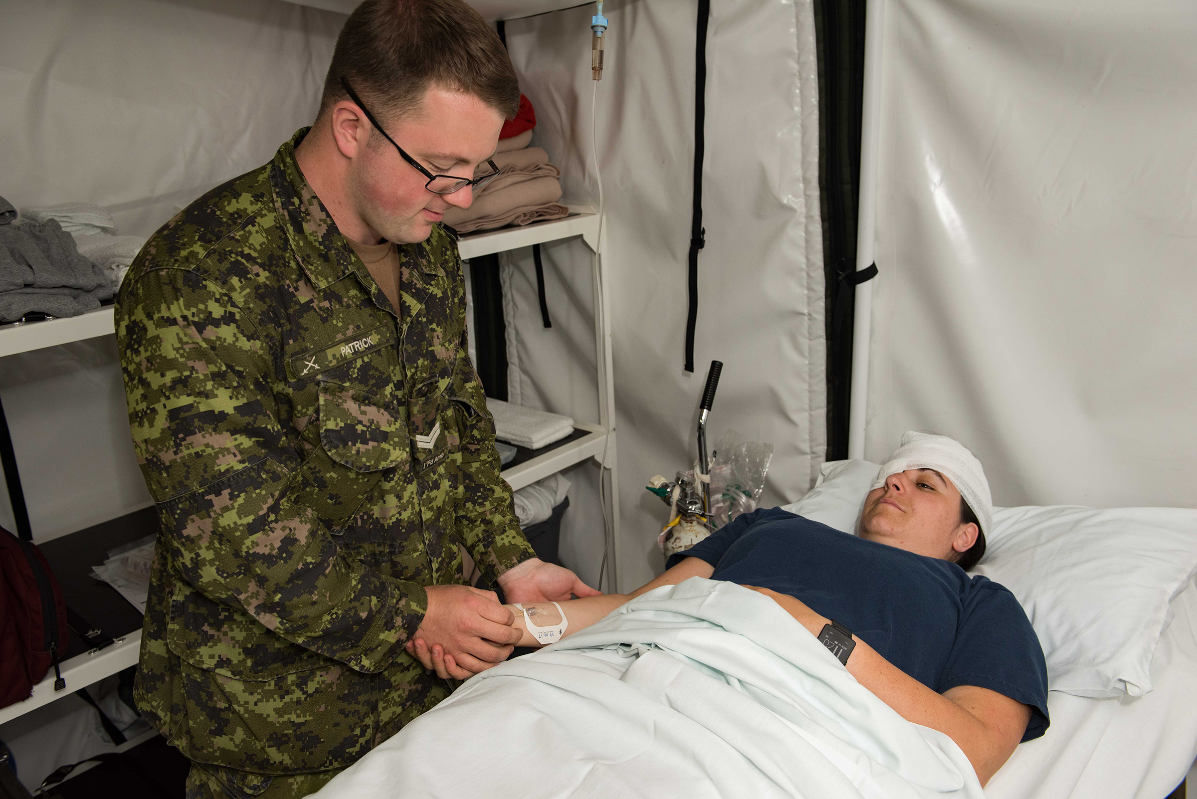 Corporal Sean Patrick, a medical technician with 1 Field Ambulance in Edmonton, Alberta, checks the intravenous fluid of a simulated patient (Corporal Sophie Renaud) in a Mobile Medical Field Hospital during Exercise Maple Flag 50 at 4 Wing Cold Lake on June 19, 2017. PHOTO: Master Corporal Heather MacRae, CK05-2017-0470-004