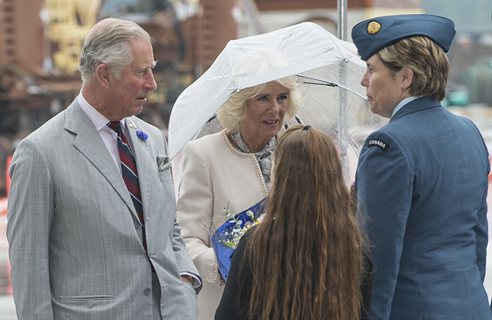 slide - A man in a gray suit and a woman in a light coloured suit, holding an umbrella, speak with a woman in a blue uniform and a young girl with long hair.