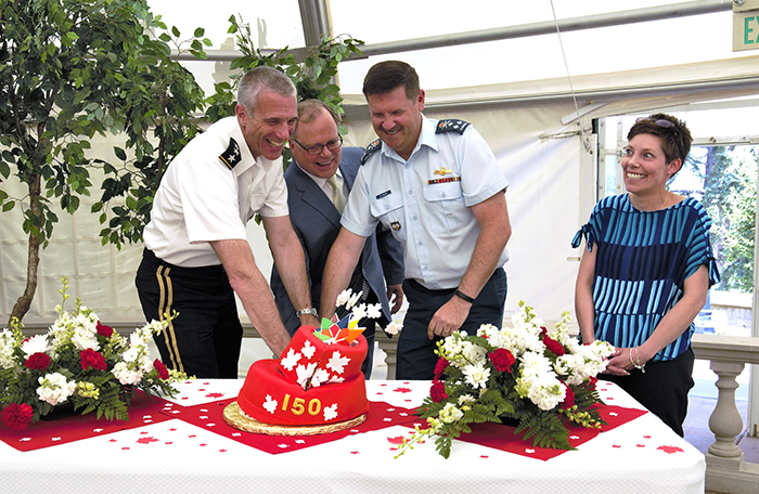 slide - Three laughing men, two in uniform and one in a suit, cut and topple a red cake with a sword, while a woman laughs.