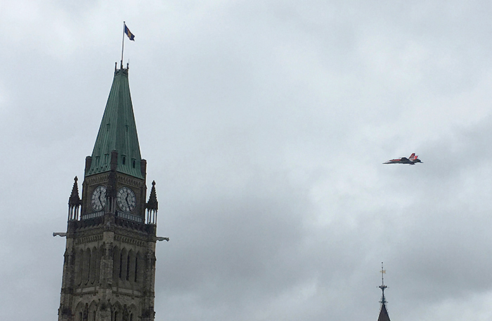 slide - A jet aircraft flies toward and behind an old stone clock tower.