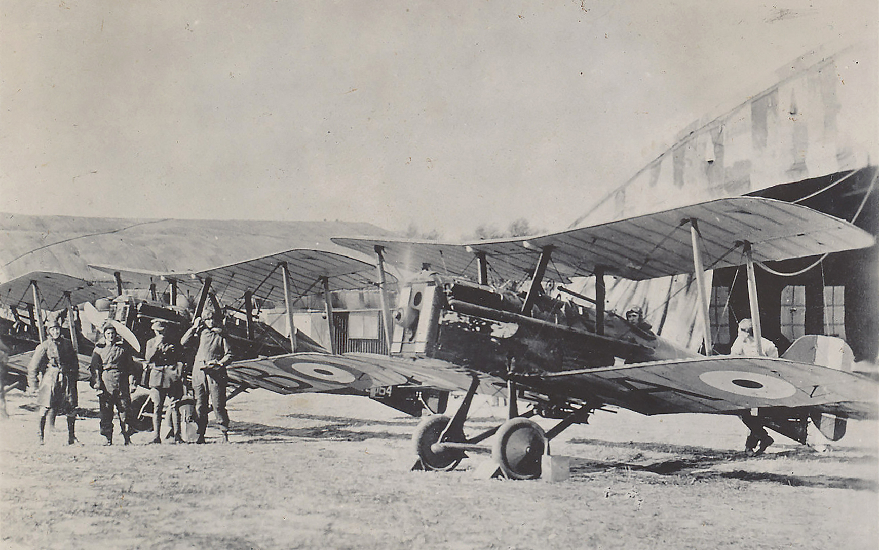 Three vintage bi-planes sit in front of old buildings, with five men standing around one aircraft with a pilot in the cockpit.