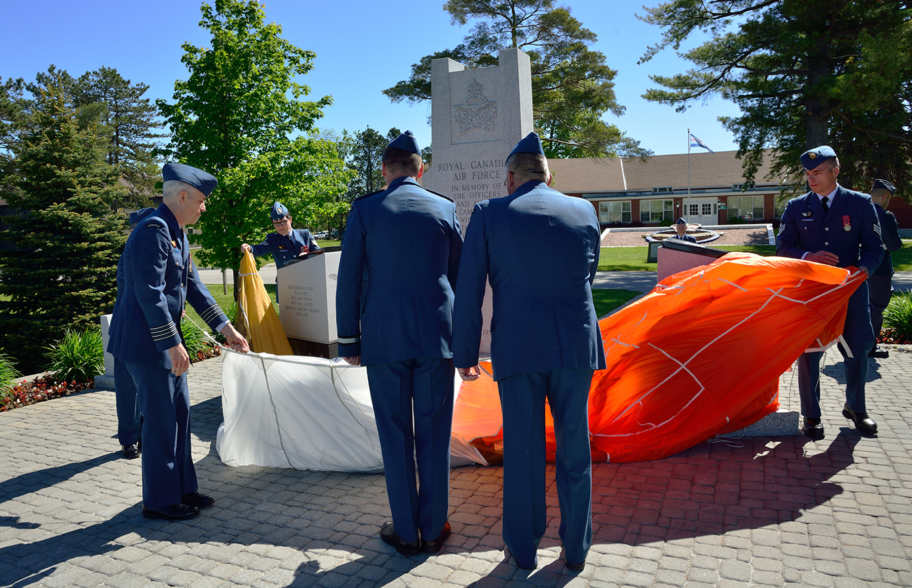 Lieutenant-Colonel Andrew Fleming (left), 16 Wing Borden, Ontario, Commander; Brigadier-General David Cochrane, 2 Canadian Air Division Commander; and Chief Warrant Officer Pierrot Jette, 2 Canadian Air Division Chief, remove the parachute from the newly rebuilt Royal Canadian Air Force Memorial on June 3, 2017, with Sergeant Patrick Lariviere (right), of the Royal Canadian Air Force Academy, assisting. PHOTO: Sergeant Christopher Bentley, BM01-2017-0174-45
