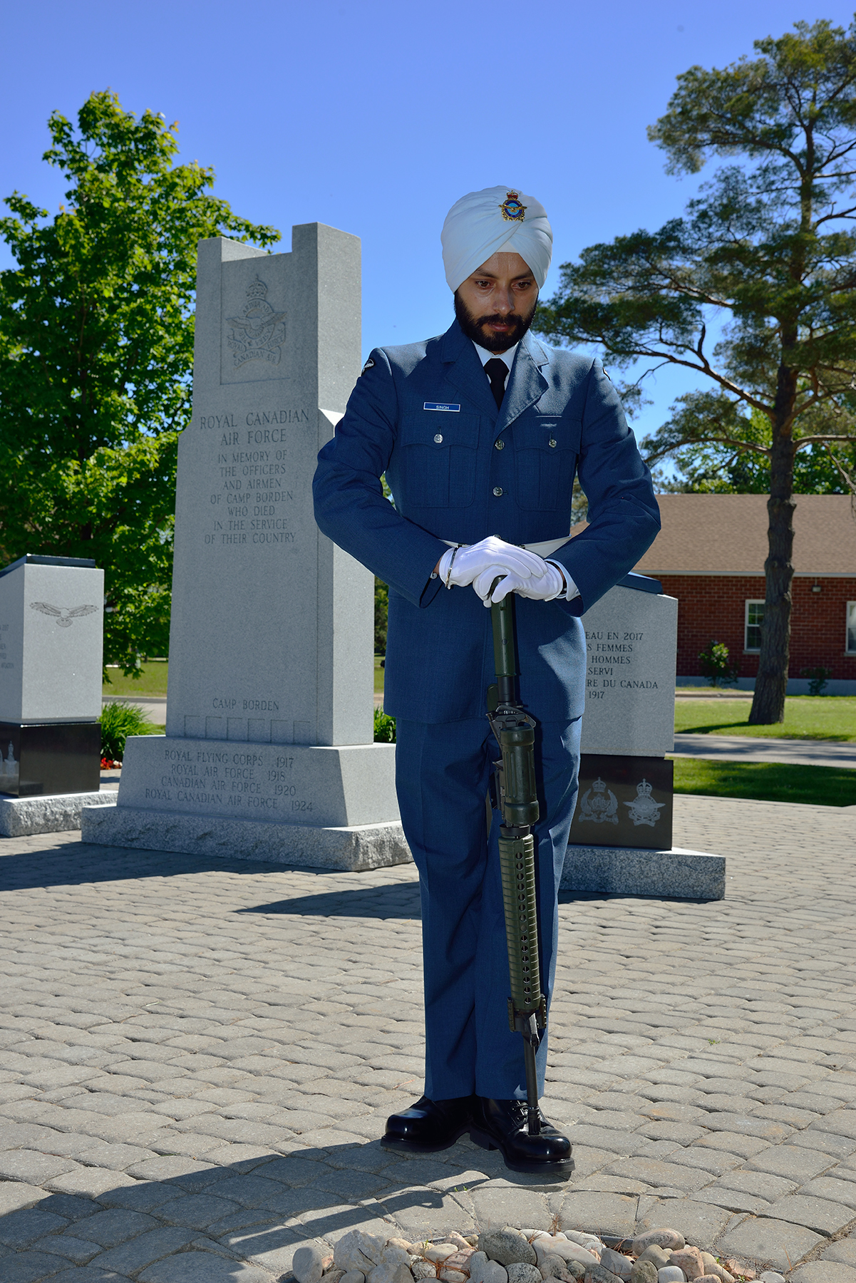 A man wearing a blue military uniform and a white turban and gloves, holding a rifle upside down with the end of the barrel on his boot-top, stands in front of a memorial.