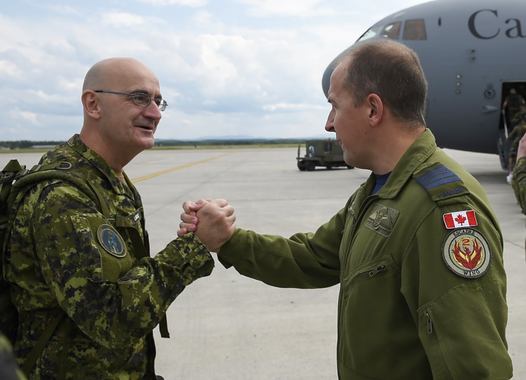 Colonel Luc Guillette, commander of 2 Wing Bagotville, bids farewell to Chief Warrant Officer Jean Lavoie, Airfield Activation Team chief warrant officer, who is departing Canadian Forces Base Bagotville, in Québec, on August 11, 2017, for his deployment to Romania on Operation Reassurance. PHOTO: Master Corporal Louis Brunet, BN25-2017-0484-015