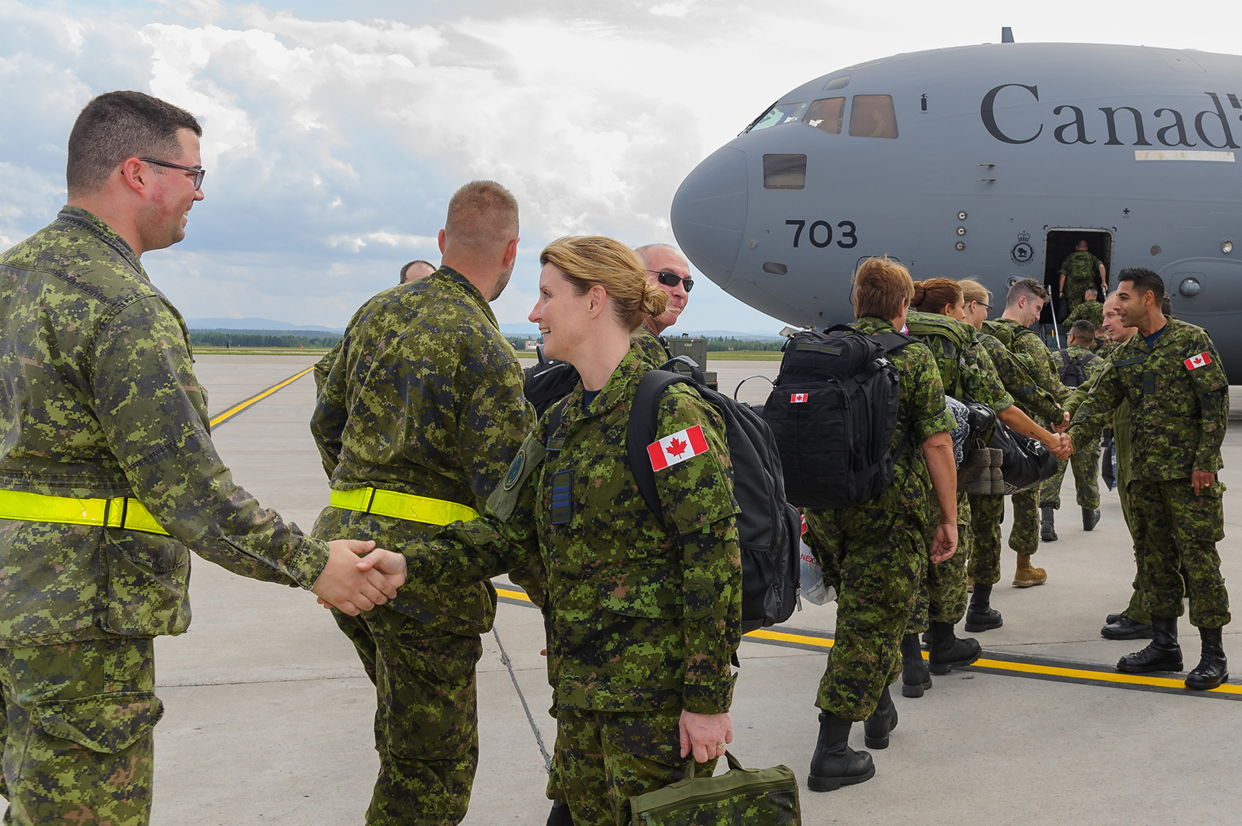 On August 11, 2017, Lieutenant-Colonel Julie Callacott, commander of 2 Wing Bagotville's Air Expeditionary Squadron and commander of the Airfield Activation Team in Romania, greets personnel who are deploying with her from CFB Bagotville, Québec, on Operation Reassurance. PHOTO: Private Mylène Bissonnette, BN10-2017-0484-010