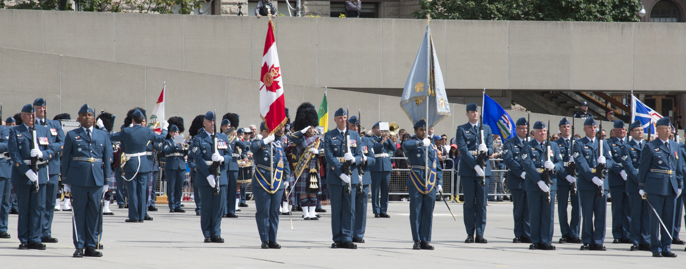 A group of military people wear blue uniforms. Two hold flags and the remainder hold rifles vertically in front of themselves. In the background, people play musical instruments while a man in full Scottish regalia salutes.