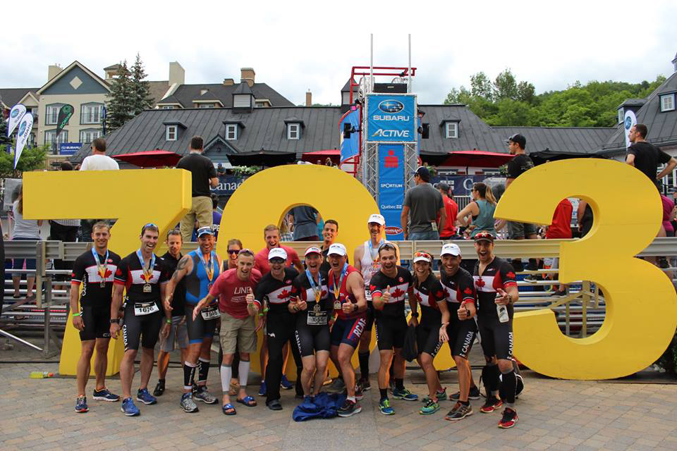 "Sixteen men and women in running gear gather for a photograph in front of large yellow numbers reading ""70.3"" and give an enthusiastic ""thumbs-up""."