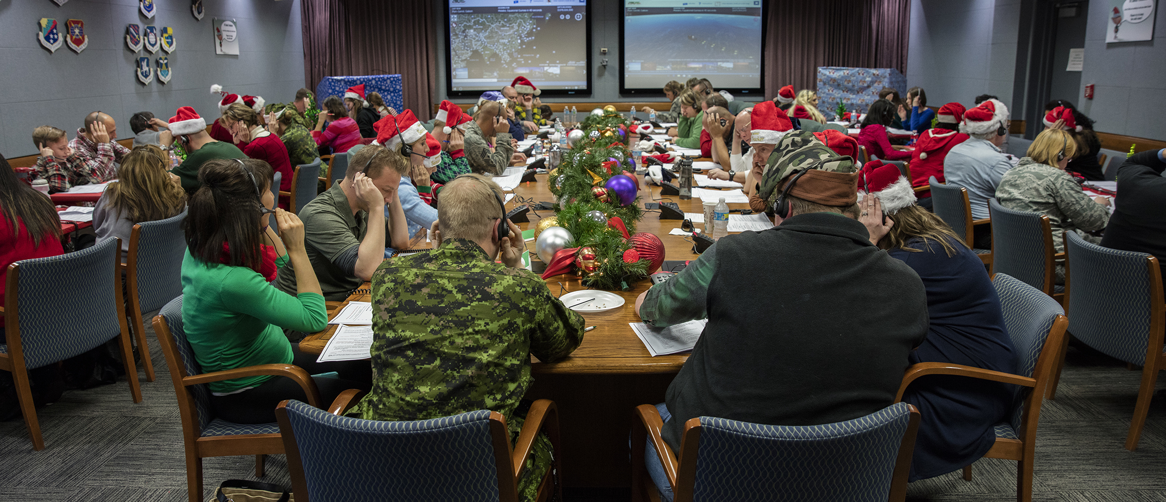 Canadian and American, military and civilian: volunteers answer phones during the 2016 NORAD Tracks Santa Event at Peterson Air Force Base in Colorado on December 24. PHOTO: Dennis Carlyle, NORAD, 161224-F-CN249-980