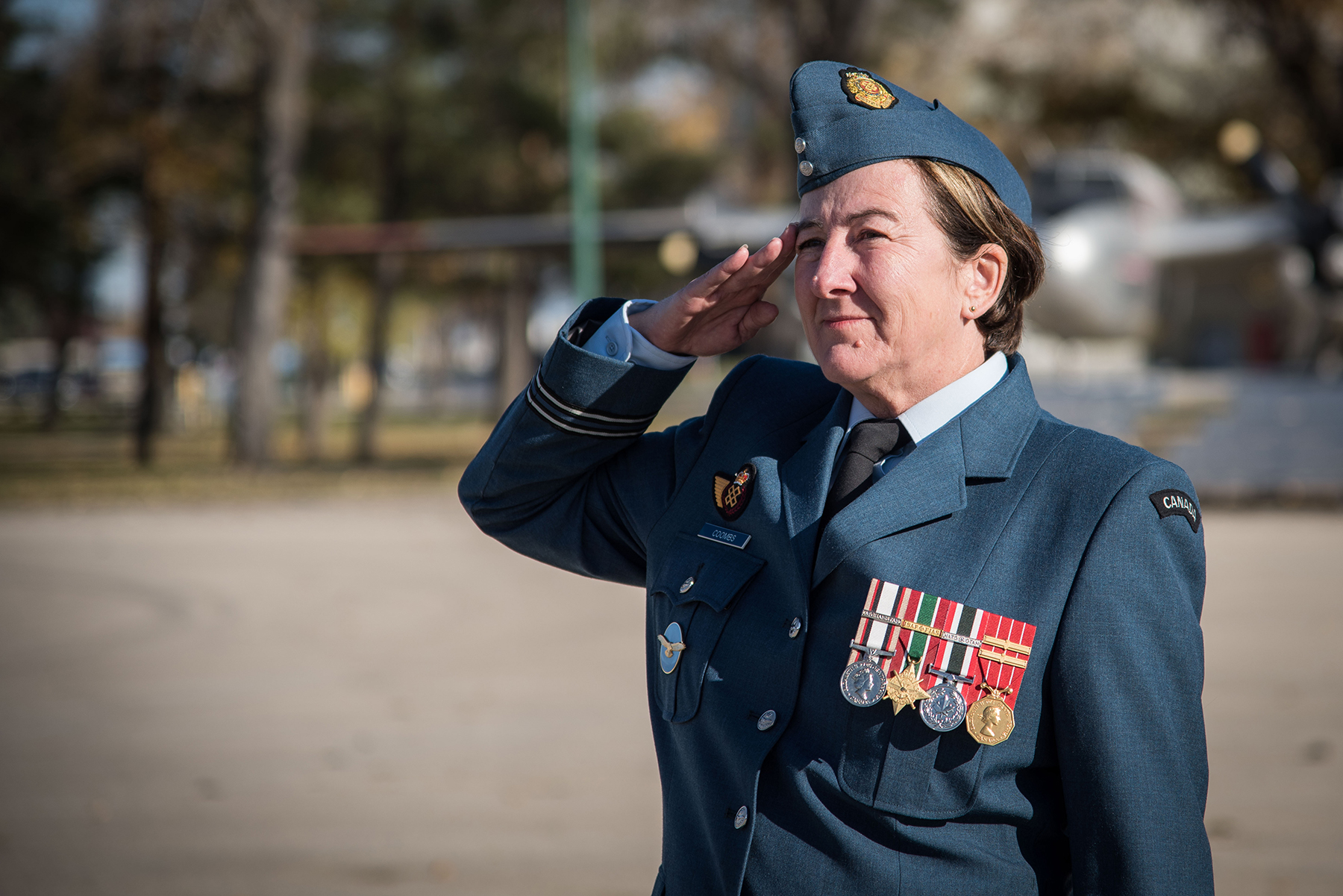 A three-quarter profile-left photograph of a woman wearing a blue uniform with four medals and saluting.