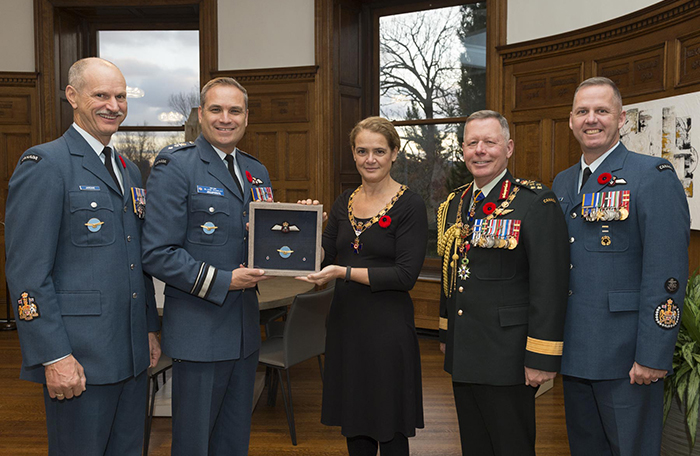 slide - A woman wearing a black dress is flanked by two men wearing military uniforms on each side. The woman and the man on her left hold a plaque that displays two winged badges.
