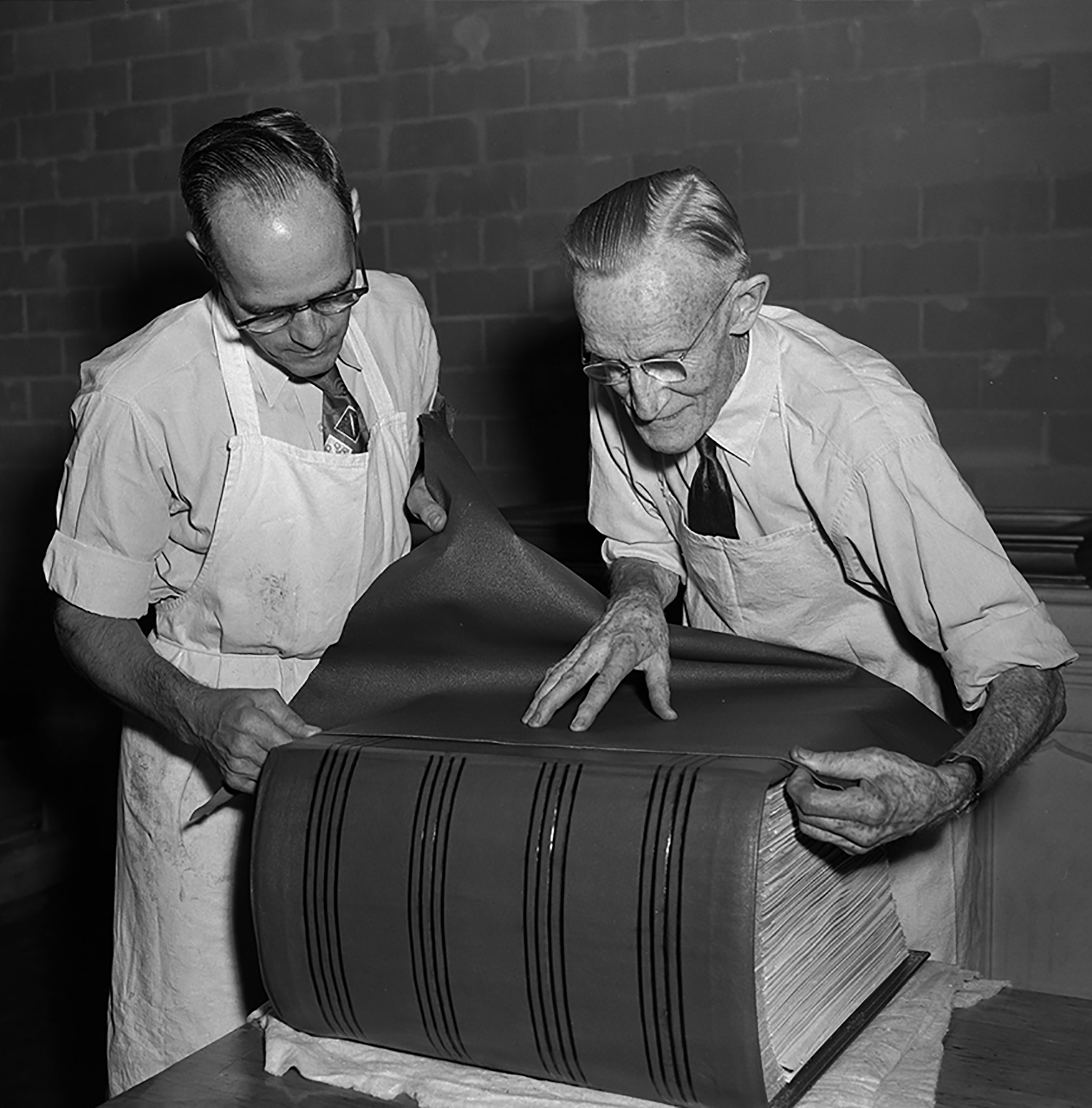 Members of the Queen's Printers staff work on the final sewing, binding and covering of Canada's Second World War Book of Remembrance. The Book, which records the names of 44,891 Canadian servicemen and servicewomen who gave their lives during the Second World War, received a leather covering, the final stage of its preparation for dedication by Governor General and Commander-in-Chief of Canada Vincent Massey in the Memorial Chamber of the Parliament Buildings in Ottawa on Remembrance Day, November 11, 1957. PHOTO: DND Archives, Z-8141-B