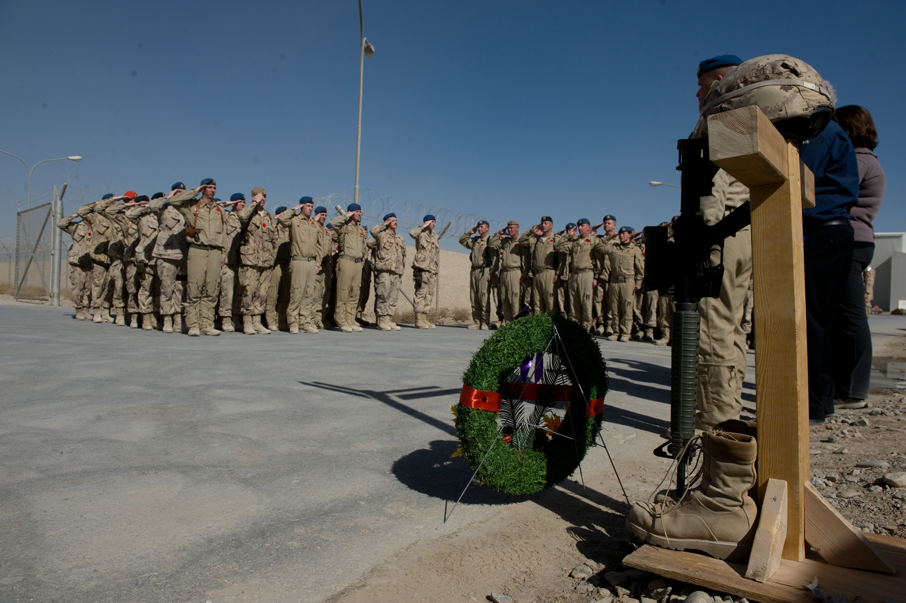 "Joint Task Force Afghanistan Air Wing personnel salute during the playing of O Canada at the November 11, 2010, Remembrance Day ceremony in Kandahar, Afghanistan. The memorial was a simple wooden cross protected by a helmet and grounded by combat boots. The JTFA Air Wing—known in Afghanistan as ""Task Force Silver Dart"", a nod to the aircraft that made Canada's first powered flight—comprised all the Canadian Armed Forces air assets in the southwest Asia theatre of operations. PHOTO: Corporal Shilo Adamson, IS2010-3037-3"