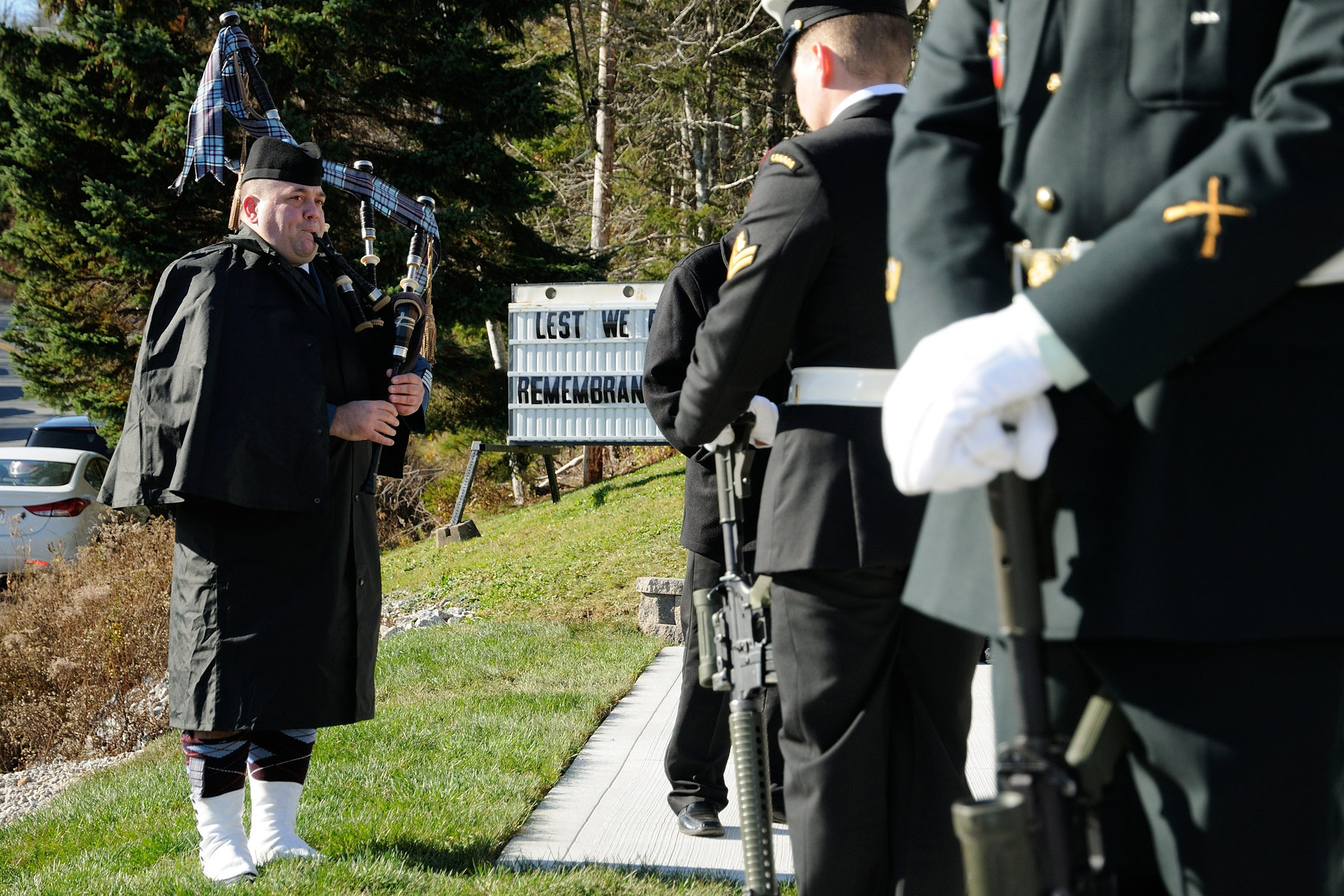 As Canadian Army members stand vigil at the cenotaph in the village of New Ross, Nova Scotia, Pipe Major Sergeant Andrew Bruce, of the 14 Wing Greenwood Pipes and Drums, plays the Lament during the November 11, 2017, Remembrance Day service. PHOTO: Sergeant Pete Nicholson, GP2017-0028
