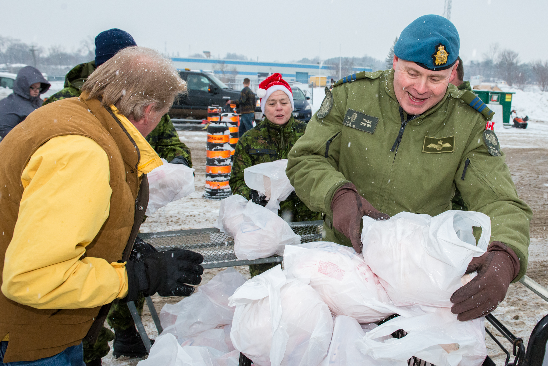 Lieutenant Colonel Russell Defer, 16 Wing Headquarters chief of staff (right), Wing Chief Warrant Officer Necole Belanger (centre), and volunteers load frozen turkeys into a cart in preparation to hand out to families during Barrie's Christmas Cheer event, at Flags Unlimited Corporation in Barrie, Ontario on December 22, 2016. PHOTO: Corporal Aydyn Neifer, BM03-2016-0389-04