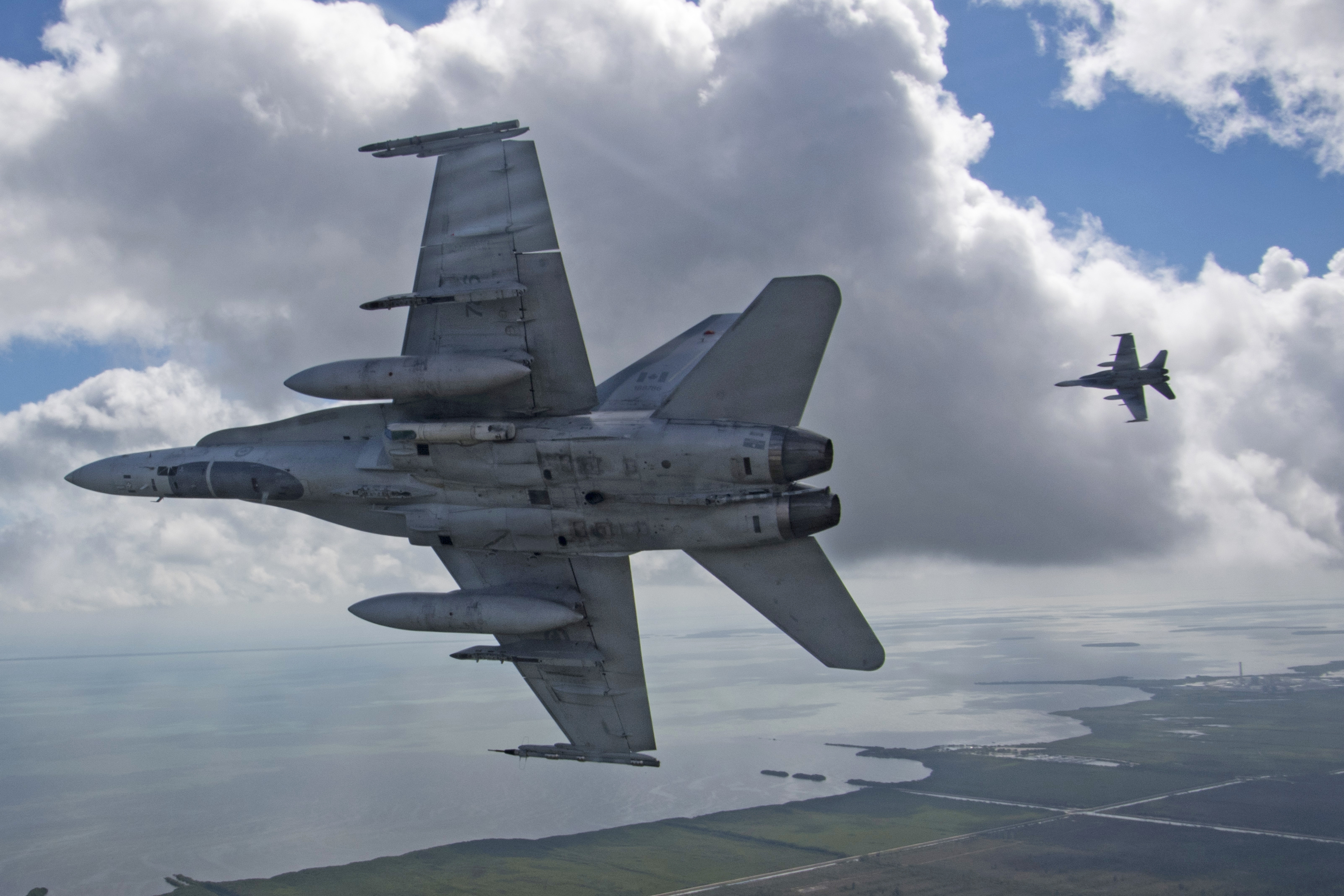 Two grey fighter aircraft in flight.