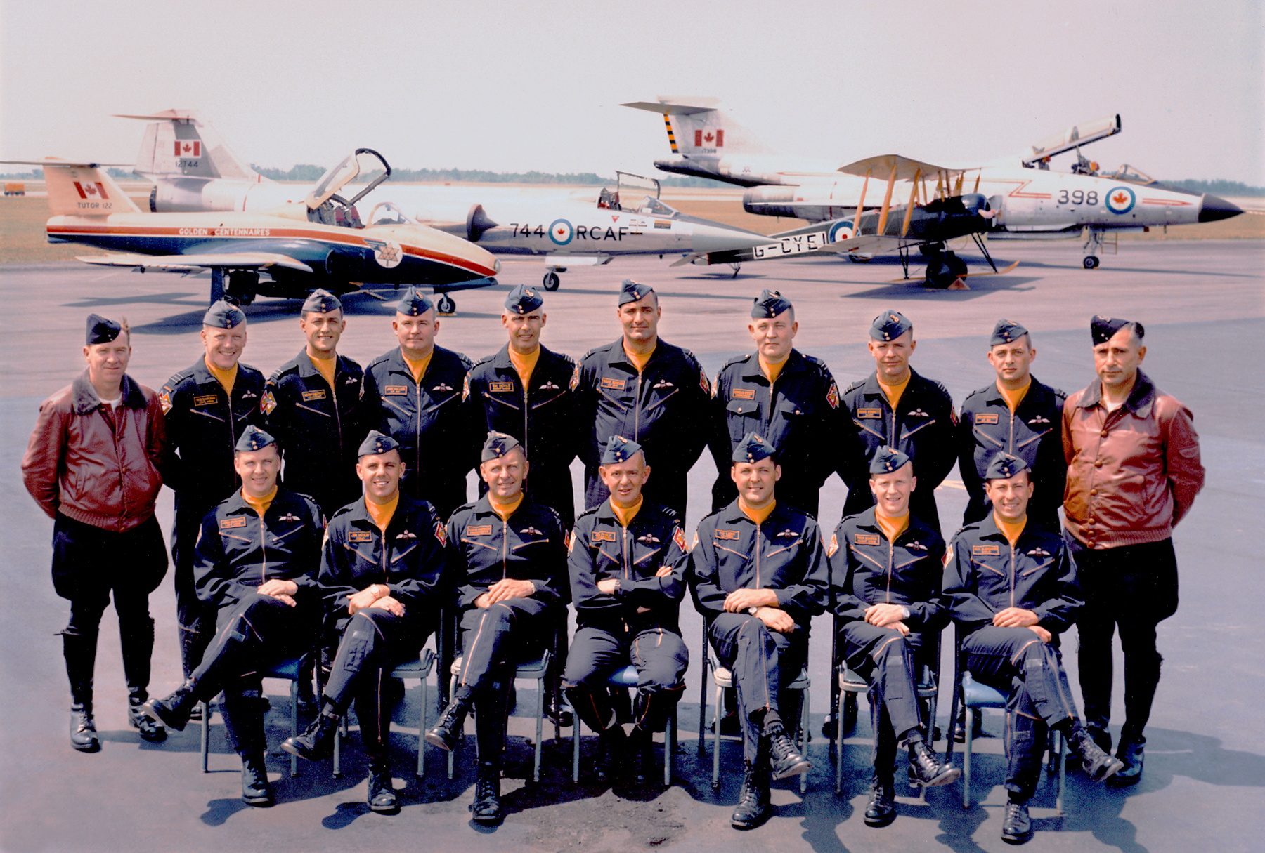 Les officiers des Paladins du Centenaire en 1967. Dans la photo, on voit, de gauche à droite, le capitaine d'aviation John Swallow (aile gauche), le lieutenant d'aviation Jim McKay (en solo à l'opposé), le commandant d'aviation Lloyd Hubbard (officier responsable des services d'information), le commandant d'escadre O.B. Philp (commandant), le commandant d'aviation C.B. Lang (chef d'équipe), le capitaine d'aviation Tom Hinton (aile droite) et le capitaine d'aviation Bill Slaughter (principal soliste). À l'arrière, à partir de la gauche, on voit le lieutenant Gord Brown (Avro 504K), le commandant d'aviation Bob Dagenais (aile extérieure gauche), le capitaine d'aviation Denis Gauthier (commentateur), le capitaine d'aviation Jake Miller (CF-101), le commandant d'aviation B.K. Doyle (aile extérieure droite), le capitaine d'aviation René Serrao (CF-104), le capitaine d'aviation Charlie Grant (officier d'ingénierie), le commandant aviation Russ Bennett, le capitaine d'aviation Rob McGsey (navigateur CF-101) et le capitaine d'aviation George Greff (Avro 504K). Sont absents le capitaine d'aviation Jack Waters (le Red Knight) et son remplaçant, le lieutenant d'aviation Rod Ellis. À l'arrière-plan se trouvent, à partir de gauche, un Tutor CT-114, un CF-104 Starfighter, un Avro 504K et un Voodoo CF-101. PHOTO : MDN, caporal Bob Imre