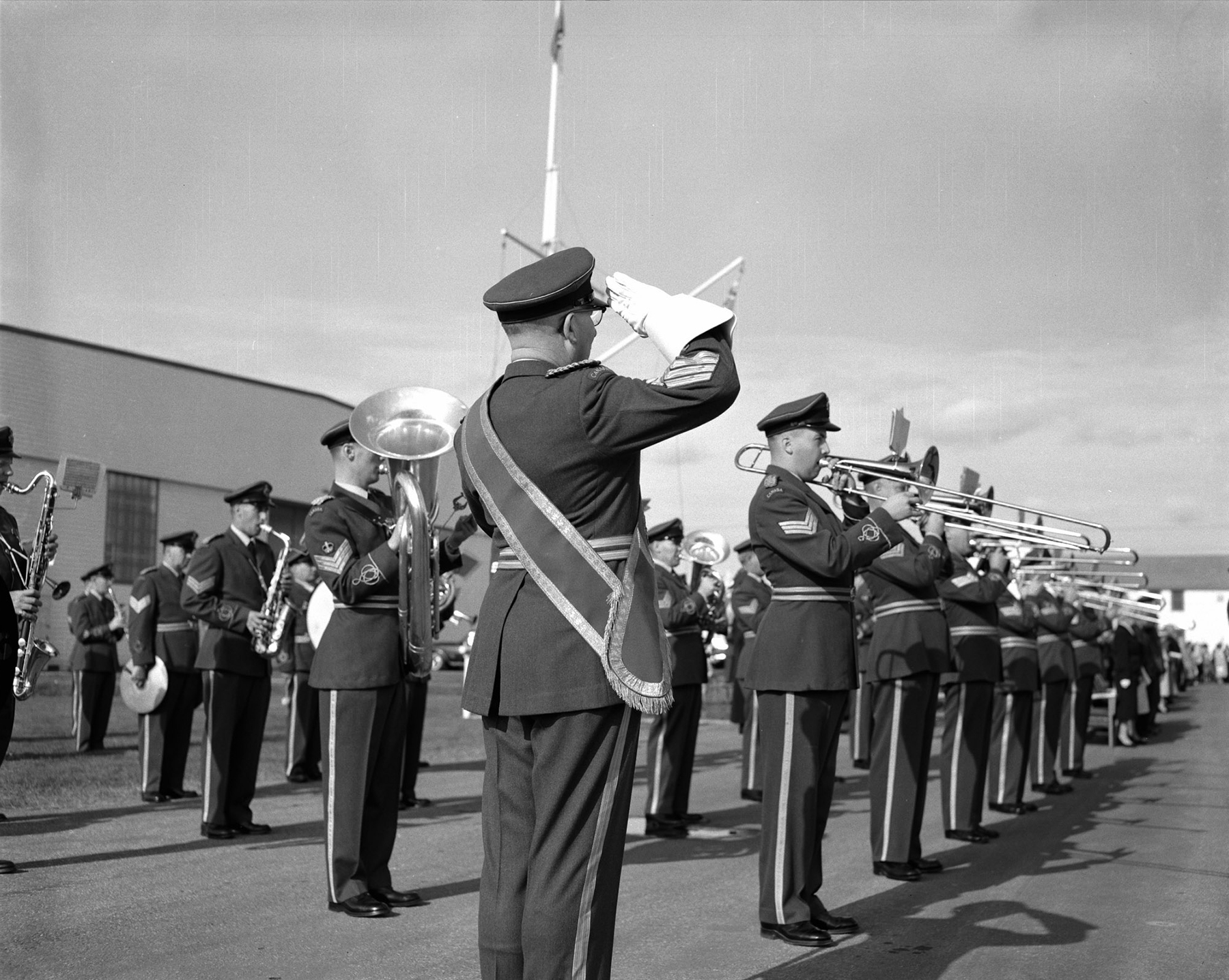 "Warrant Officer second class J.C. Reid salutes as the Training Command Band sounds ""Last Post"" and ""Rouse"" during the Battle of Britain Parade at RCAF Detachment Kingsway in Edmonton, Alberta, on September 20, 1959. PHOTO: DND Archives, PL-77424"