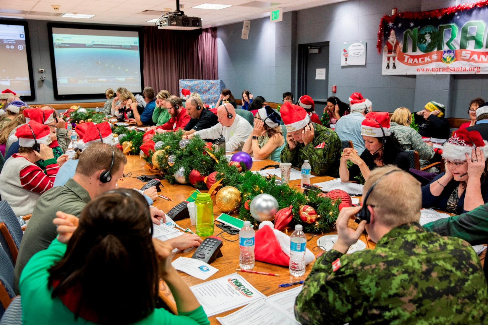 Canadian and American, military and civilian: volunteers answer phones during the 2016 NORAD Tracks Santa Event at Peterson Air Force Base in Colorado on December 24. During the 2016 NTS event, 1,500 volunteers answered 150,000 phone calls, 2,800 emails and 3,000 On-Star requests from children around the world who asked about Santa's location and when he would arrive at their house. PHOTO: Dennis Carlyle, NORAD, 161224-F-CN249-166