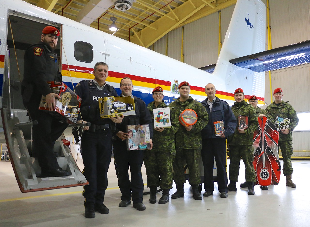 Santa's helpers! RCMP and members of 25 Military Police Flight at 5 Wing Goose Bay, Newfoundland and Labrador, stand in front of the RCMP Twin Otter that will be used to deliver toys to children in remote communities such as Nain, Natuashish and Hopedale. PHOTO: Makala Chapman