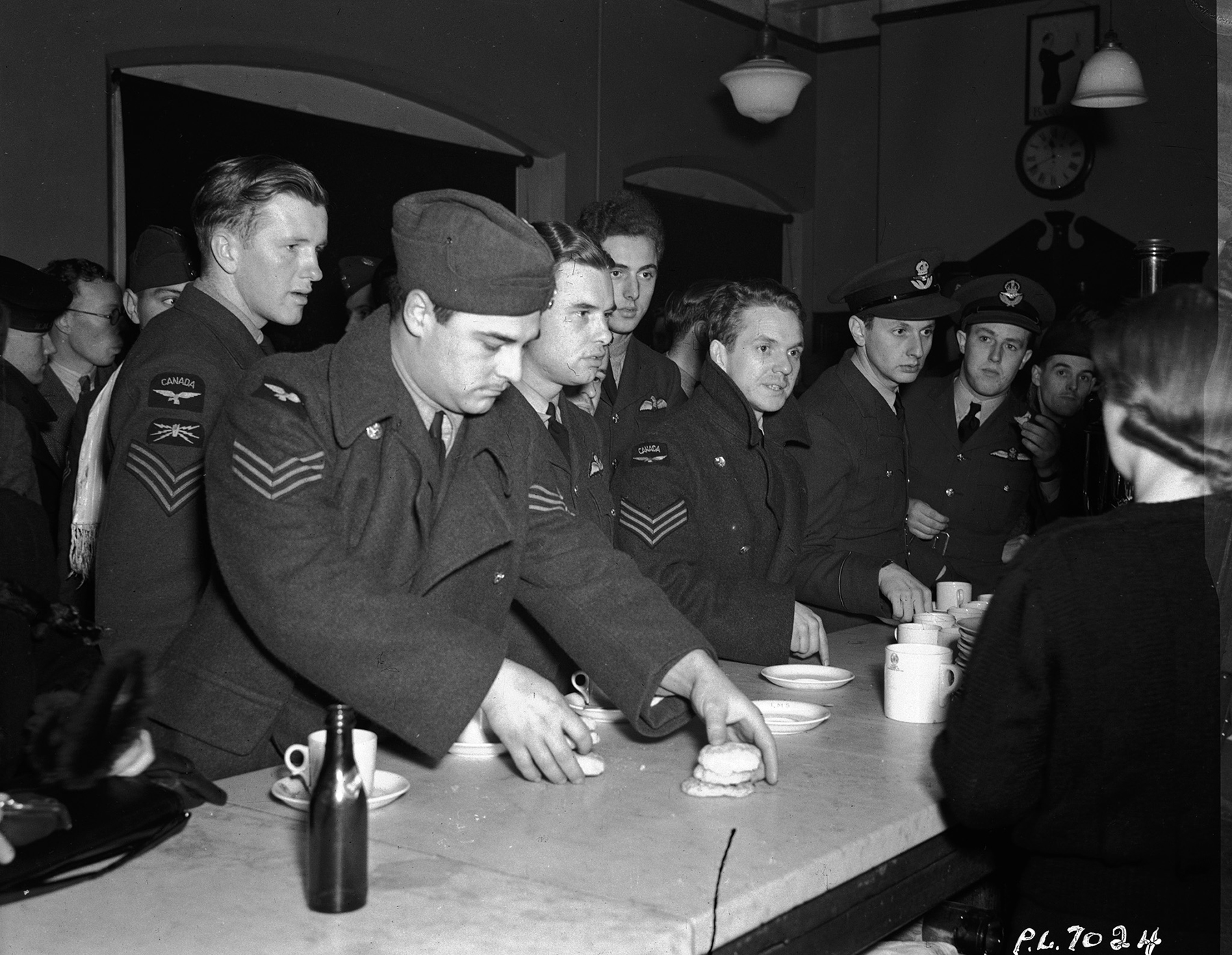 """Come and get it!"" is the order for all hands on December 26, 1941, as members of the Royal Canadian Air Force throng the restaurant car on a British troop train following disembarkation. They made up the largest RCAF draft to sail overseas, and arrived in time for Christmas. PHOTO: DND Archives, PL-7024"
