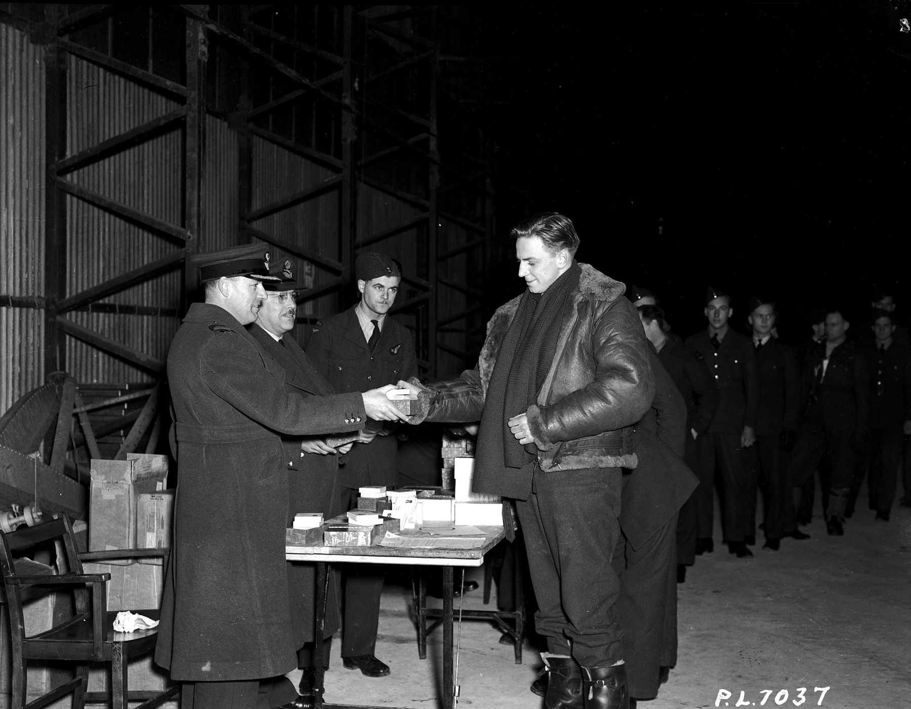 Sergeant Air Gunner A.J. Francis of Saskatoon, Saskatchewan, receives a Christmas gift on December 25, 1941, from Group Captain W.A.D. Brock, who is the commanding officer of the RAF station from which a Canadian bomber squadron operates. PHOTO: PL-70337
