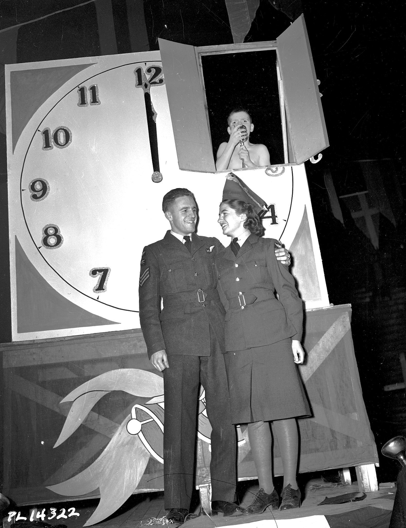 "Sergeant Lloyd Winters, a wireless air gunner from North Bay, Ontario, and Aircraftwoman Second Class Frances Beehler, from Woodstock, New Brunswick, greet the new year under the supervision of ""Young 1943"" at the New Year's dance at the Royal Canadian Air Force #1 Manning Depot in Toronto, Ontario. The event was the largest New Year's Eve function in Toronto, with attendance estimated at between 8,000 and 10,000 RCAF members and friends dancing to the music of the RCAF orchestra. PHOTO: DND Archives, PL-14322"