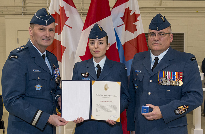 slide - Three people wearing air force uniforms stand beside each other. Two are jointly holding a certificate in a folder.