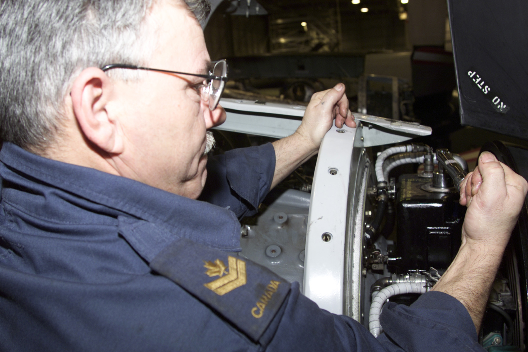 On February 14, 2001, Royal Canadian Air Force aviation technician Master Corporal Fred Masson, of the Air Reserve Augmentation Force attached to 413 Transport and Rescue Squadron at 14 Wing Greenwood, Nova Scotia, changes a propeller valve housing filter on one of the engines of a CC-130 Hercules aircraft as a routine part of the aircraft's inspection cycle. PHOTO: DND, IHD01-0066