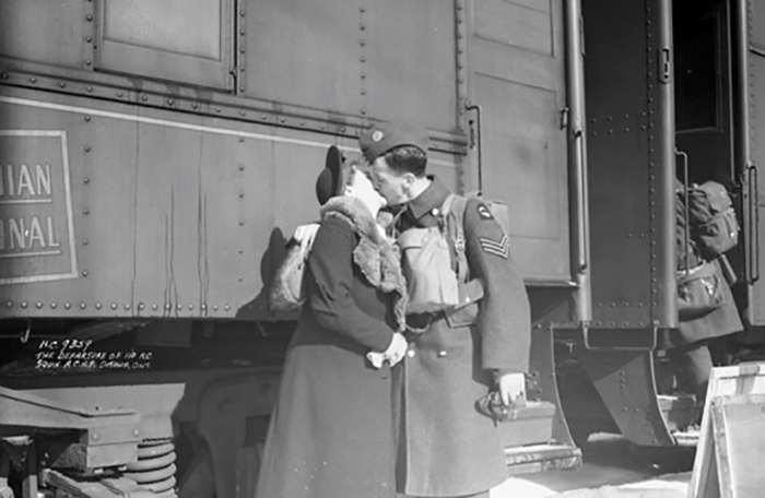 slide - In a vintage photograph, a man and woman kiss beside a train.