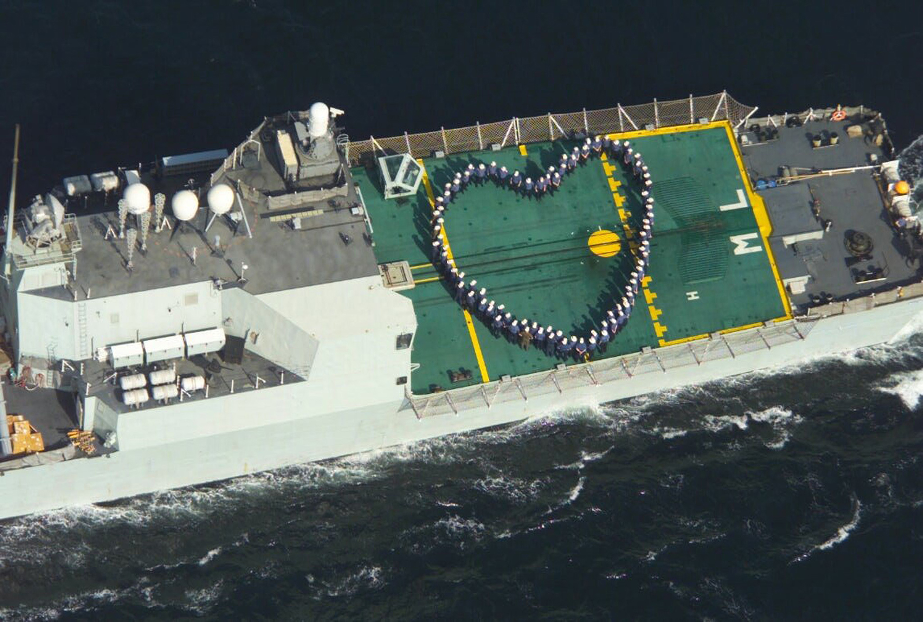 On board Her Majesty's Canadian Ship Montreal, deployed personnel find an original way to wish their families a happy Valentine's Day on February 14, 2003, by making the shape of a heart on the ship's flight deck, normally occupied by the CH-124 Sea King helicopter from which the photo is being taken. PHOTO: DND, PM2003-0017