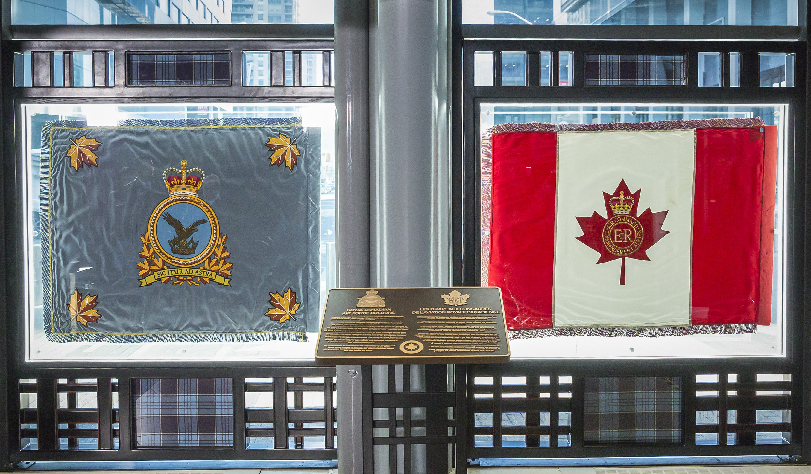 Two flags are displayed flat inside a glass wall with a plaque on a pedestal in front of them.